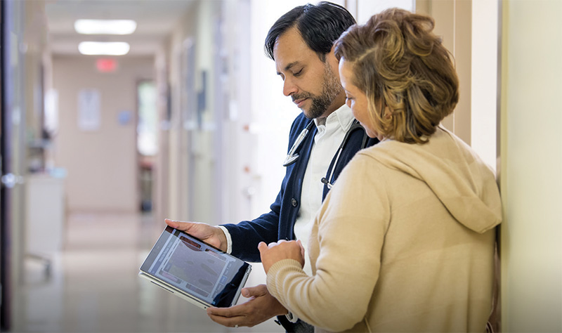 Man in hallway showing medical namiation on the HP EliteBook to a woman